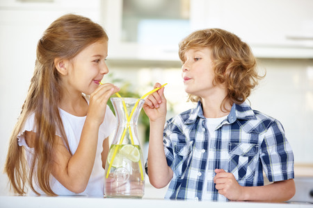 carafe: Two children drinking fresh water with straw in the kitchen