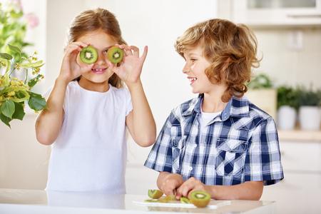 nonsense: Two happy kids having fun with kiwi in a kitchen