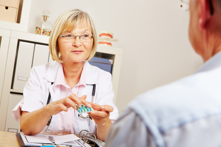 dosage: Female doctor telling recommended dosage for medication to a patient Stock Photo