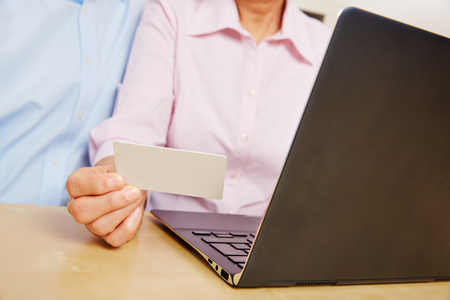 electronically: Hand holding customer credit card while shopping online with laptop computer