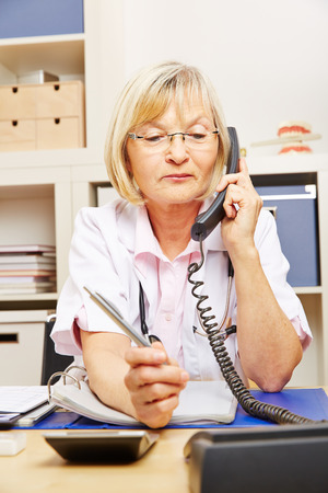 telephone call: Old female doctor on call sitting in her office at the telephone Stock Photo