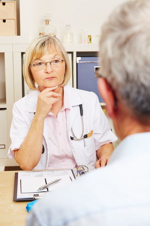pangs: Doctor listening to patient in the office during consultation Stock Photo