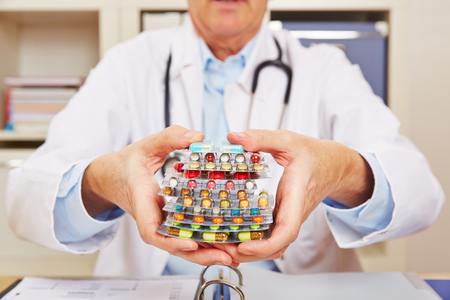 Doctor holding many different colorful pills in in hands Stock Photo - 57526702