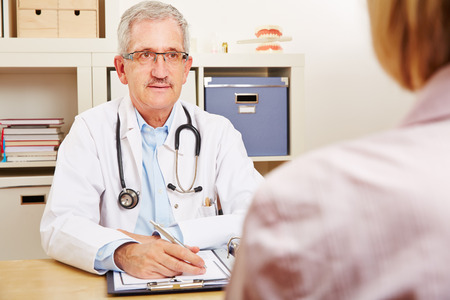 pangs: Old doctor talking with patient during a medical consultation Stock Photo