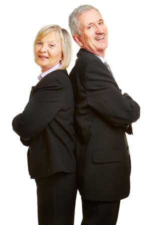 senior citizen woman: Happy senior couple as businesspeople leaning back to back with their arms crossed