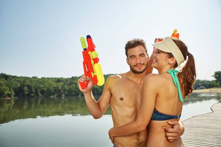 squirt: Couple with squirt guns hugging each other in summer Stock Photo