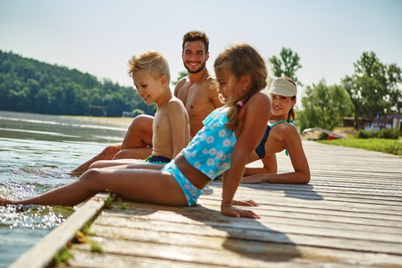 Family on a holiday at a lake in summer cooling their feet Stock Photo