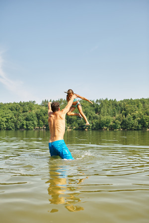 nonsense: Father throws daughter in the water at the lake on the summer