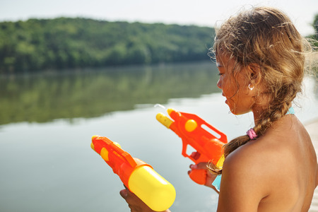 squirt: Girl playing with a squirt gun at a lake on the summer holidays