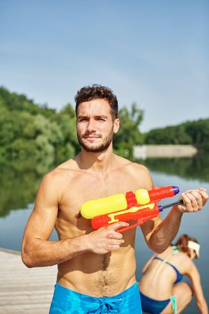 squirt: Happy couple with squirt guns at the lake in summer
