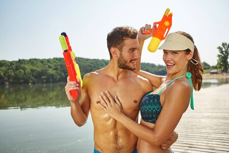 couples hug: Couple at a lake having fun with squirt guns in summer
