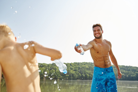 nonsense: Happy father and son spray each other with water at a lake in summer Stock Photo