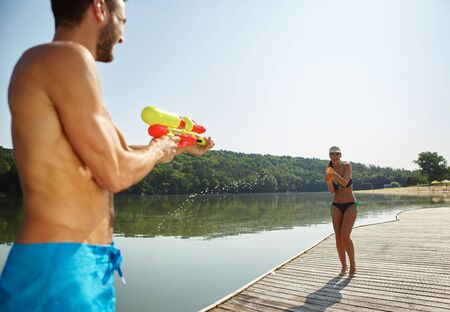 nonsense: Happy couple at a lake spraying each other with a water gun in summer Stock Photo
