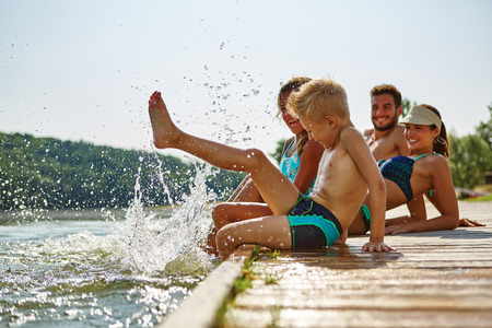 Familie Baden und Spritzwasser mit ihrem Fuß an einem See im Sommer