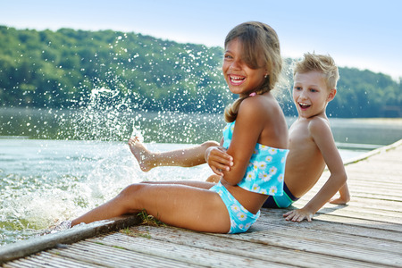 shore: Two children splashing with water in summer