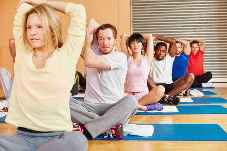 Mensen die zich uitstrekt tijdens fitness klasse in de fitnessruimte Stockfoto