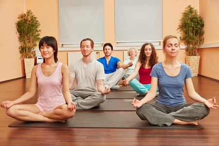 tailor seat: Group of people during yoga meditation breathing exercise class Stock Photo