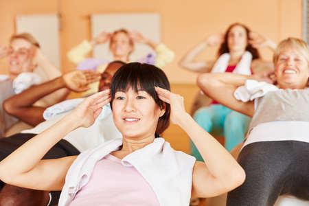 women sport: Woman making pilates exercise during class together with other people Stock Photo