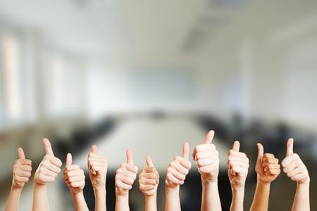 Mensen houden duimen omhoog in een vergaderruimte op hun kantoor