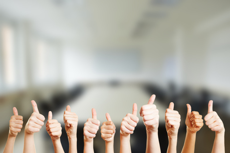 People holding thumbs up in a conference room at their office