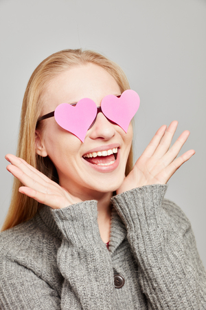 Woman in love sees two pink hearts over her eyes Stock Photo