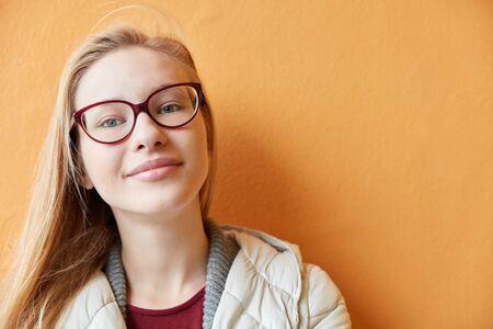 Une jeune femme souriante et blonde se tient face à un mur d'orange