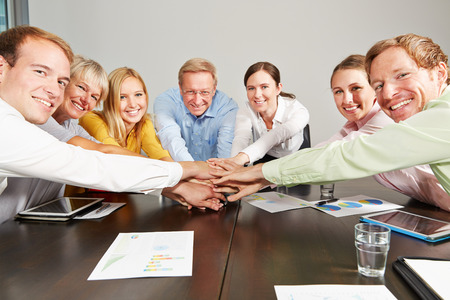 Many business people stacking their hands for motivation in the office