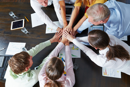 Many business people from above stacking hands as teamwork concept