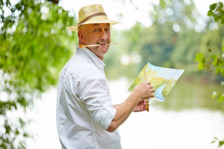acrylic: Senior painter in nature with brush painting a picture in summer