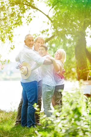ancianos felices: Feliz grupo de personas mayores de pie en el jardín de la casa de retiro en verano