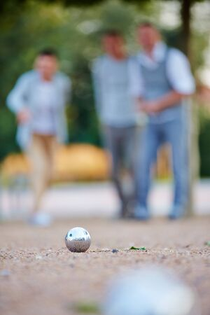 couples outdoors: Metal ball of boule game laying in sand Stock Photo