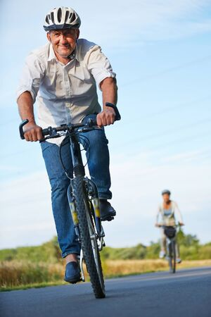 healthy path: Senior people with bike helmets cycling in summer