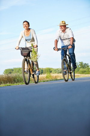 Two smiling senior people riding bikes in summer on a bike path Foto de archivo