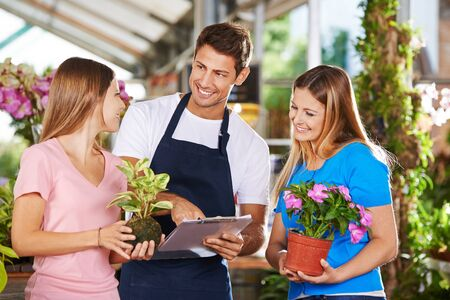 flower nursery: Salesman and customers in a nursery shop talking to each other Stock Photo