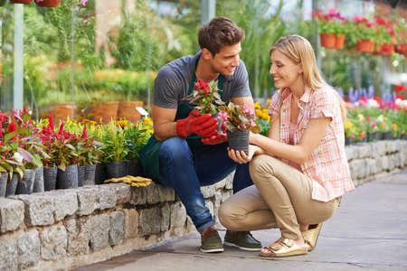 garden center: Smiling woman talking to gardener in garden center about different flowers