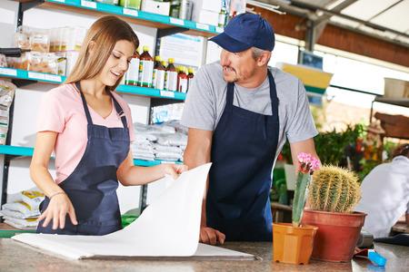 apprenticeship employee: Young woman as gardener trainee in a nursery shop