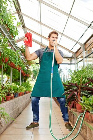 garden staff: Happy gardener singing in water hose in a greenhouse