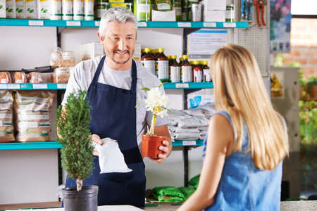 Salesman recommending woman a fertilizer for orchid plant in nursery photo