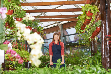 garden staff: Smiling gardener with apron working in a nursery shop Stock Photo