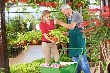 Woman getting quaity consultation from gardener in a garden center photo