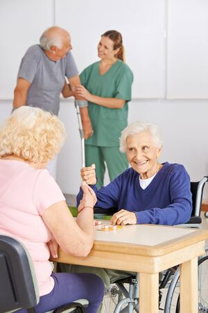 care allowance: Two senior people playing Bingo together in a nursing home