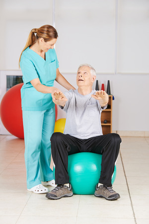 gym ball: Senior man doing fitness exercise in physiotherapy on a gym ball