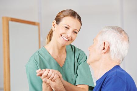 terapia ocupacional: Enfermera sonriente de la mano geriátricos con hombre mayor de edad