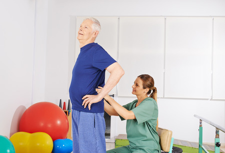 chronic back pain: Old man with chronic back pain getting treatment in physiotherapy praxis Stock Photo