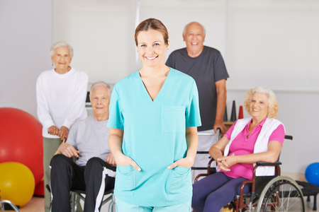 Smiling geriatric nurse standing in front of a happy group of senior people Imagens