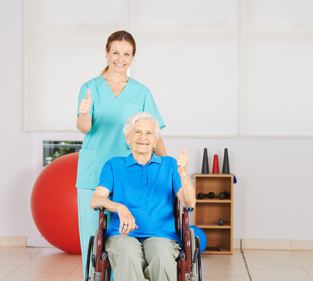 mobility nursing: Happy old woman in wheelchair holding her thumbs up with geriatric nurse