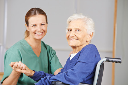 outpatient: Geriatric nurse and senior woman in wheelchair smiling together in nursing home