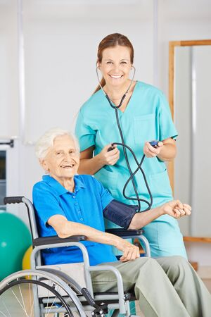 eldercare: Smiling nurse measuring blood pressure of old woman in a wheelchair Stock Photo