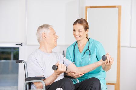 terapia ocupacional: anciano en silla de ruedas de levantamiento de pesas en la fisioterapia