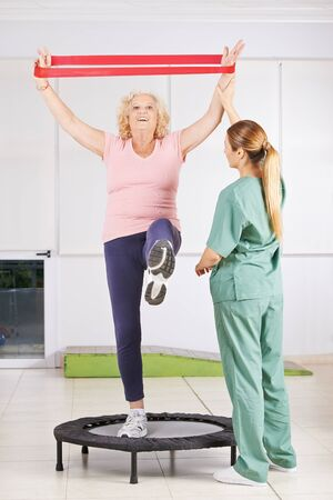 trampoline: Old woman exercising with latex band in physiotherapy Stock Photo